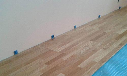 Установка клинышек для создания зазора между стеной и ламинатом